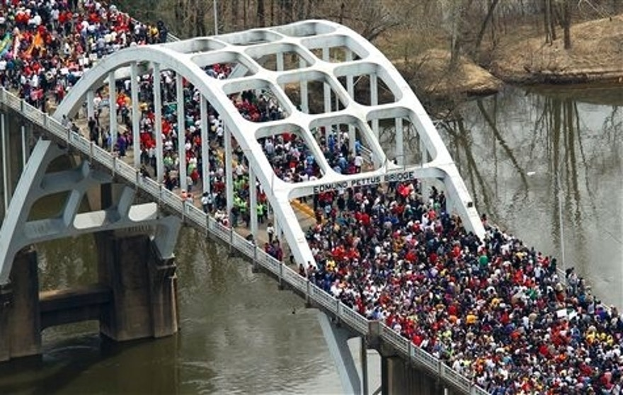 "In this aerial view, Crowds of people move in a symbolic walk across the Edmund Pettus Bridge, Sunday, March 8, 2015, in Selma, Ala. This weekend marks the 50th anniversary of ""Bloody Sunday,' a civil rights march in which protestors were beaten, trampled and tear-gassed by police at the Edmund Pettus Bridge, in Selma.  (AP Photo/Butch Dill)"