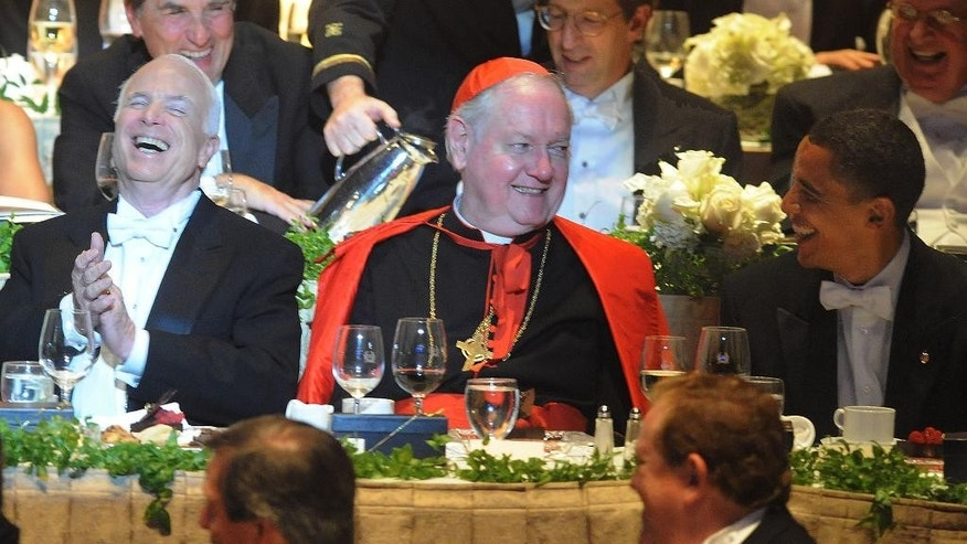FILE -  In this Oct. 16, 2008, file photo, New York Cardinal Edward Egan, center, joins candidates Sens. John McCain, left, and Barack Obama at the 63rd Annual Alfred E. Smith Foundation Dinner in New York. Egan, the former archbishop of New York, died, Thursday, March 5, 2015, of cardiac arrest in New York. He was 82. (AP Photo/Andrew Theodorakis, Pool, File)