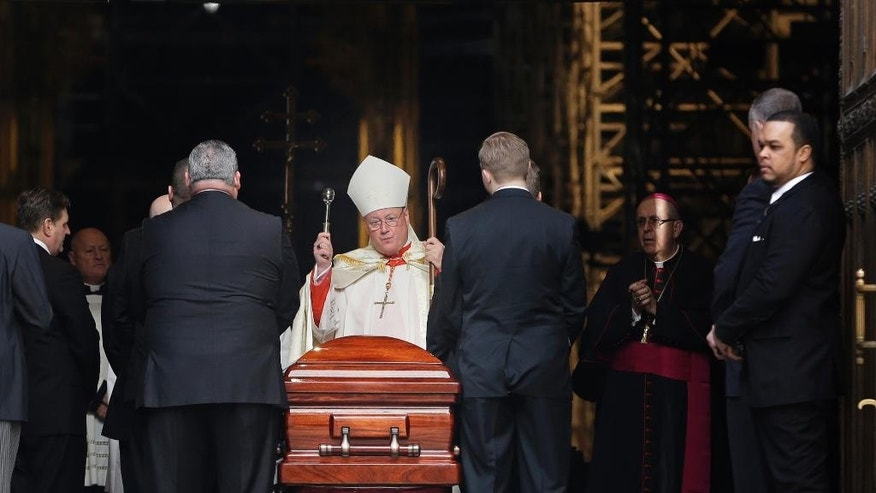 Cardinal Timothy Dolan, the current archbishop of New York, center, sprinkles holy water on a casket containing the body of Cardinal Edward Egan at St. Patrick's Cathedral in New York, Monday, March 9, 2015. Egan played a prominent role in New York City after the Sept. 11 terror attacks, and now New Yorkers are preparing to pay respects to the former archbishop after his death last week. (AP Photo/Seth Wenig)