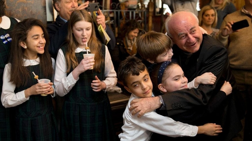 "Archbishop Vincenzo Paglia embraces students before sampling milkshakes during a news conference to pick a milkshake for the upcoming World Meeting of Families, Monday, March 9, 2015, at a Potbelly Sandwich Shop in Philadelphia. Paglia met with about a dozen students at the shop in downtown Philadelphia to pick the milkshake that would benefit planning efforts for September's event. Paglia, the president of the council in charge of the event, settled on the flavor ""#PopeInPhilly.""  Pope Francis will attend the closing event Sept. 26 of the world meeting. The next day he'll celebrate an outdoor Mass.   Fifty cents from every shake sold at three locations will benefit planning for the events.  (AP Photo/Matt Rourke)"