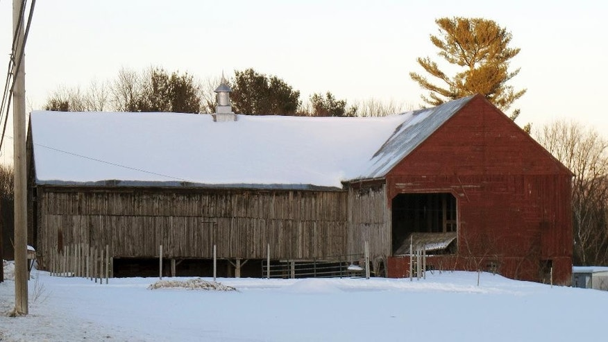 In this Feb. 27, 2015 photo, the barn where Orville Gibson disappeared on the morning of New Year's Eve 1957 sits alongside on U.S. Route 5 in Newbury, Vt. Almost 60 years after he disappeared and was later found dead, a retired Vermont judge is arguing in a new book that Gibson's death was a suicide. For decades many thought Gibson's death was vigilante revenge for his beating of a hired man. But Gibson's surviving relatives still believe he was murdered and there could be people in town who know who did it. (AP Photo/Wilson Ring)