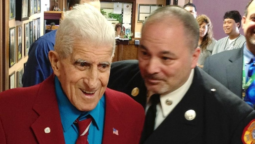 World War II veteran Alfred Bettencourt, left of Cranston, R.I., smiles as he arrives at his surprise medal ceremony Monday, March 9, 2015, in Johnston, R.I. Bettencourt was wounded in France but didn't receive the Purple Heart until now because his records were lost. Cranston fire Captain Chuck Pollock, right, helped Bettencourt recover his records. (AP Photo/Amy Anthony)
