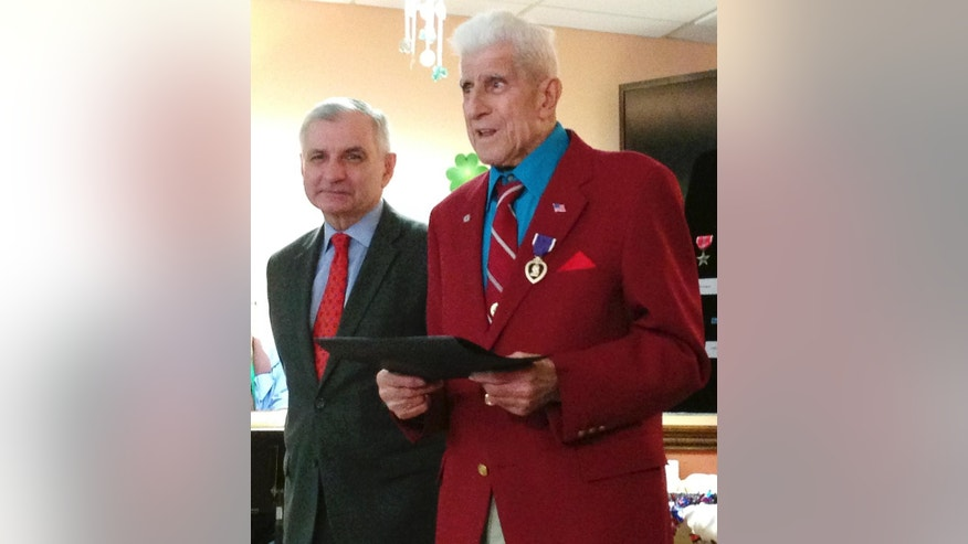 U.S. Sen. Jack Reed, left, stands with World War II veteran Alfred Bettencourt, of Cranston, R.I. after pinning his Purple Heart during a surprise medal ceremony Monday, March 9, 2015, in Johnston, R.I. Bettencourt was wounded in France but didn't receive the Purple Heart until now because his records were lost. Cranston fire Captain Chuck Pollock helped Bettencourt recover his records. (AP Photo/Amy Anthony)