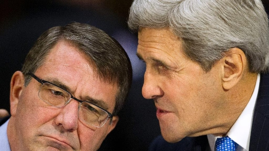 Secetary of State John Kerry, right, leans in to talk with Defense Secretary Ash Carter, on Capitol Hill in Washington, Wednesday, March 11, 2015, as they prepare to testify before the Senate Foreign Relation Committee. America's top national security officials face questions on Capitol Hill about new war powers being drafted to fight Islamic State militants, Iran's sphere of influence and hotspots across the Mideast.(AP Photo/Pablo Martinez Monsivais)