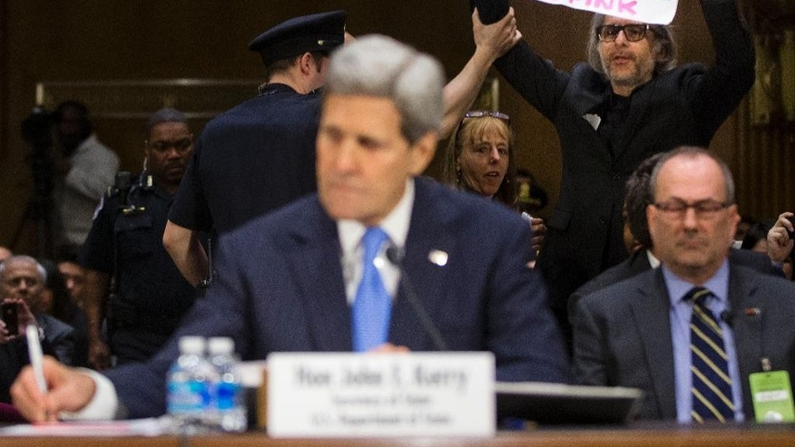 A CodePink demonstrator holds up a sign on Capitol Hill in Washington, Wednesday, March 11, 2015, as he attempts to disrupted the testimony of Secretary of State John Kerry at a hearing before the Senate Foreign Relation Committee. Three of America's top national security officials face questions on Capitol Hill about new war powers being drafted to fight Islamic State militants, Iran's sphere of influence and hotspots across the Mideast. (AP Photo/Pablo Martinez Monsivais)