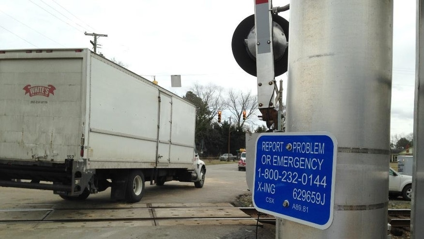 A truck passes over the train tracks near a sign listing an emergency number for railroad problems on Tuesday, March 10, 2015, in Halifax, N.C.  A train collided with a truck, Monday injuring 55 people.  The truck with a state trooper escort become stuck in the crossing but no calls were made to Amtrak about the problem, even though the sign should have been visible to the truck driver.  (AP Photo /Jonathan Drew)