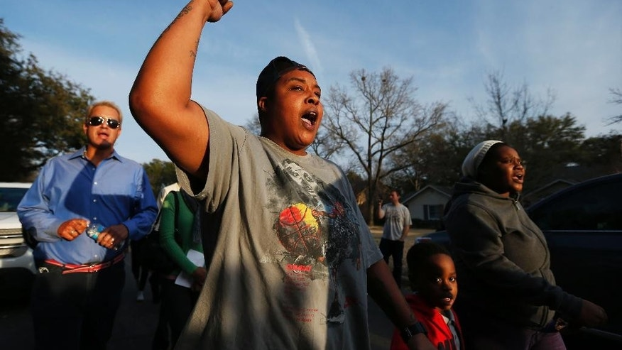 Charletteria Mathis, second from left, Albeta Wellington, far right, and her son Mark Wallace, 5, protest outside the family home of a former University of Oklahoma Sigma Alpha Epsilon fraternity member Parker Rice, Wednesday, March 11, 2015, in Dallas. Rice and several other fraternity members were seen on video chanting a racist song. (AP Photo/Brandon Wade)