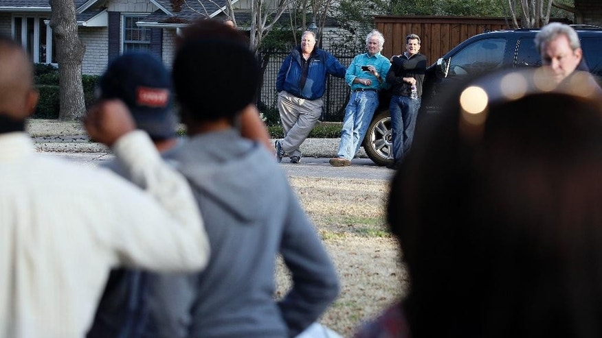 Area residents look on as protesters march outside the family home of a former University of Oklahoma Sigma Alpha Epsilon fraternity member Parker Rice, Wednesday, March 11, 2015, in Dallas. Rice and several other fraternity members were seen on video chanting a racist song. (AP Photo/Brandon Wade)