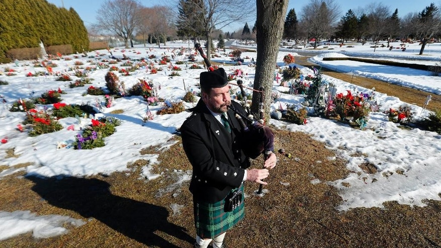 Donald Ross plays bagpipes at the funeral service for a newborn, known simply as Baby Henry, Wednesday, March 11, 2015, in Clinton Township, Mich. A fire department honor guard, local leaders and members of the public attended to pay their respects to Baby Henry, whose lifeless body was discovered almost two months ago at a Detroit-area recycling center. Police say 24-year-old Angela Alexie gave birth Dec. 22 in an Eastpointe garage and left the baby. The body was found Jan. 14 at a Roseville recycling center. Alexie is charged with murder. (AP Photo/Paul Sancya)