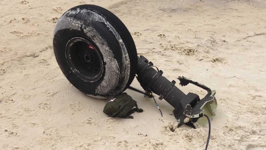 Part of a wheel assembly of what could be the wreckage of a UH-60 Black Hawk helicopter sits on on Riviera Beach in Navarre, Fla., Wednesday, March, 11, 2015.  Human remains washed ashore in heavy fog Wednesday after seven Marines and four soldiers were believed to be killed in an Army helicopter crash during a night-time training mission in Florida. (AP Photo/Northwest Florida Daily News, Jennie McKeon)