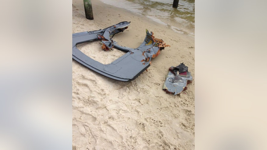 Part of a door assembly of what could be the wreckage of a UH-60 Black Hawk helicopter sits on Riviera Beach in Navarre, Fla., Wednesday, March, 11, 2015.  Human remains washed ashore in heavy fog Wednesday after seven Marines and four soldiers were believed to be killed in an Army helicopter crash during a night-time training mission in Florida. (AP Photo/Northwest Florida Daily News, Jennie McKeon)