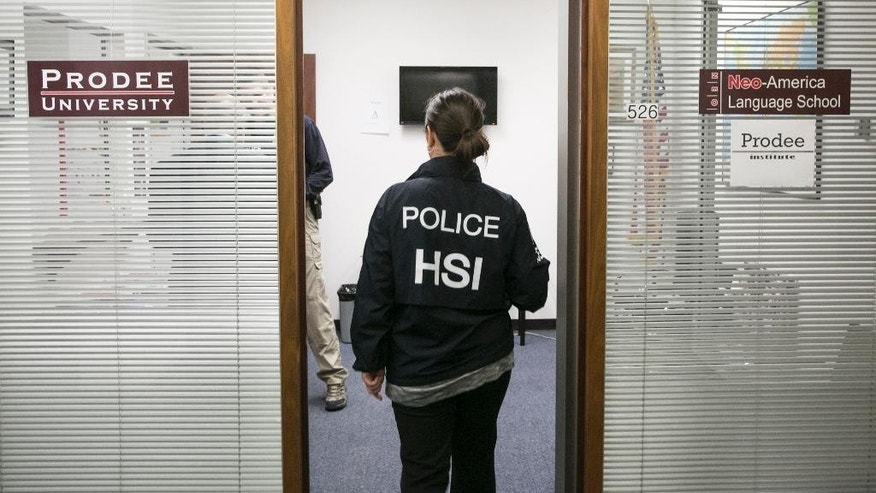 U.S. Department of Homeland Security Investigations agents raid the Prodee University, Neo America Language School installations in Los Angeles on Wednesday, March 11, 2015. Three people were arrested on charges of running four sham vocational schools in Southern California that issued fraudulent paperwork enabling foreigners to stay in the country and netted as much as $6 million a year. (AP Photo/Damian Dovarganes)