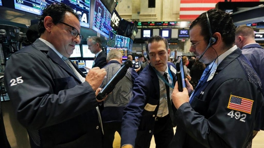 Gregory Rowe, center, squeezes between fellow traders as he works on the floor of the New York Stock Exchange, Wednesday, March 11, 2015. U.S. stock indexes are opening slightly higher, a day after a big sell-off prompted by worries about higher U.S. interest rates. (AP Photo/Richard Drew)
