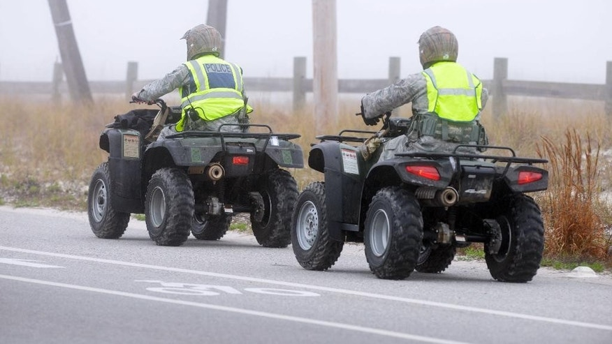 Unidentified military personnel ride all-terrain vehicles at Navarre Beach, Fla., Wednesday, March 11, 2015 as they search for survivors from an Army Black Hawk helicopter that went down near this Florida panhandle community Tuesday evening with 11 service members aboard. (AP Photo/Northwest Florida Daily News, Devon Ravine)