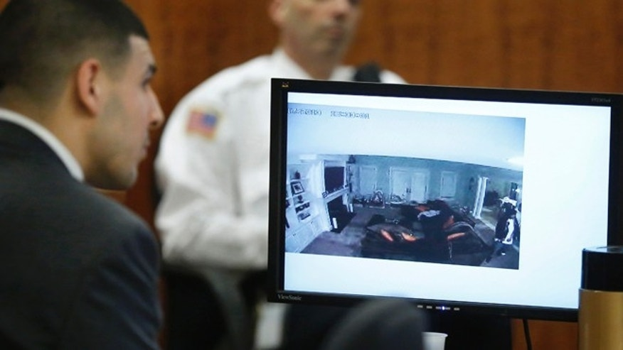 March 12, 2015: Former New England Patriots football player Aaron Hernandez, left, watches as a still frame from surveilance video is displayed on a monitor during his murder trial.