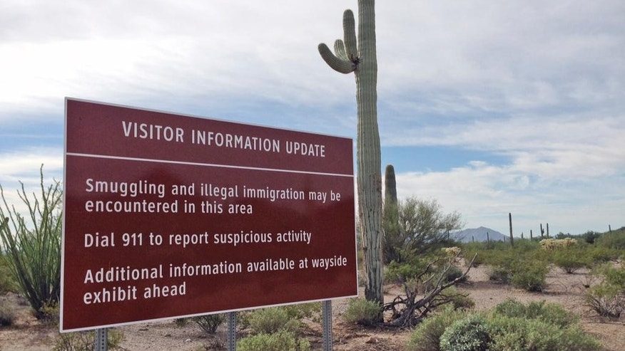 In this October 30, 2014 photo, a sign warns visitors of smuggling and illegal immigration at the Organ Pipe Cactus National Monument in Arizona. For over a decade, armed drug traffickers were so prevalent in this vast desert monument that visitors were barred from entering more than half of it. But a series of crackdowns and decreased traffic on Arizona's border with Mexico have turned things around at the national monument. For the first time since 2003, the picturesque park is fully accessible, all 516 square miles of its sweeping mountains and cactus-covered terrain. (AP Photo/Astrid Galvan)