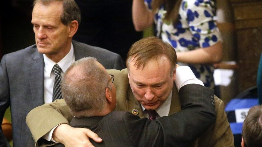 ADDS MORE INFO - Sen. Stephen Urquhart, left, R-St. George, embraces Sen. Jim Dabakis, D-Salt Lake City, after the Republican-controlled Utah Legislature passed an anti-discrimination bill Wednesday, March 11, 2015, in Salt Lake City. A Mormon-church-backed anti-discrimination bill that protects LGBT Utah residents and religious rights received final approval at the state's Republican-controlled Legislature on Wednesday. Utah's Republican-controlled Legislature also has passed a bill that allows county clerks to refuse to marry same-sex couples for religious reasons. But the bill requires a county clerk's office to designate someone who will marry gay couples if the clerk opts out. (AP Photo/Rick Bowmer)