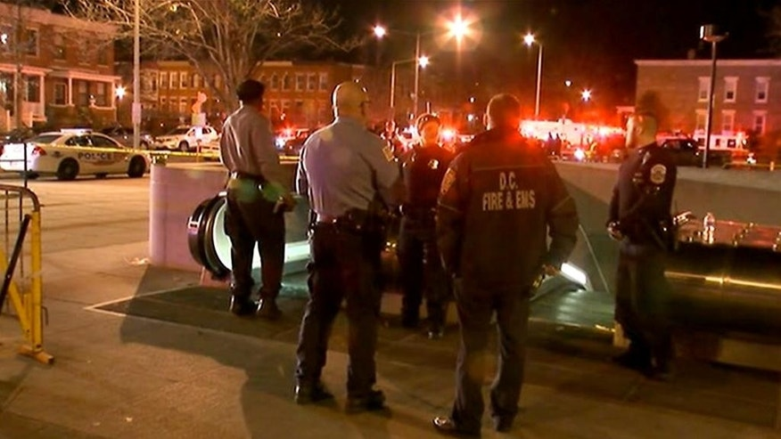 "In this still image taken from video, police and fire officials stand outside the entrance to the Potomac Avenue Metro Station, Thursday night, March 12, 2015 in Washington.  Transit police in Washington, D.C. fatally shot a man after responding to a call about an ""unauthorized person"" on the tracks in a subway tunnel.  (AP Photo/WJLA-TV)"