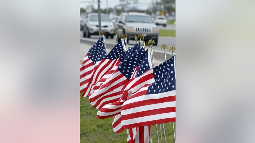 American flags stand along U.S. Highway 98 in Navarre, Fla., Thursday, March 12, 2015, one for each service member missing following Tuesday night's crash of an Army Black Hawk helicopter near this small Florida panhandle community. (AP Photo/Northwest Florida Daily News, Devon Ravine)