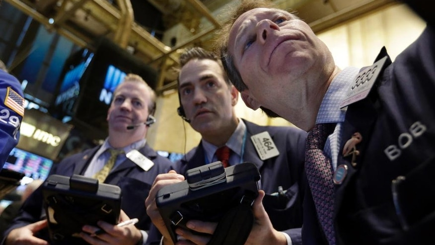 Traders gather at a post on the floor of the New York Stock Exchange, Friday, March 13, 2015. U.S. stocks are opening slightly lower a day after the market notched its best performance in five weeks. (AP Photo/Richard Drew)
