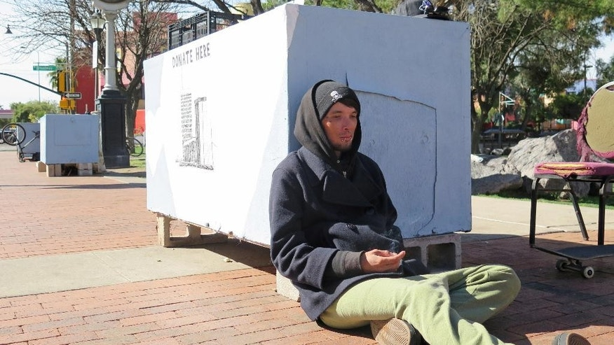 "In this Feb. 25, 2015 photo, Sonny Clenny, 29, sits near a ""dream pod"" in downtown Tucson, Ariz., at a park where protesters have made a permanent home. The protesters at Veinte de Agosto Park say the growing encampment on a small, one-acre green space is a way to combat city regulations they believe unfairly target the homeless. For city officials and business owners, it's an eyesore that unfairly takes space away pedestrians and chases away visitors and tourists and their dollars. (AP Photo/Astrid Galvan)"