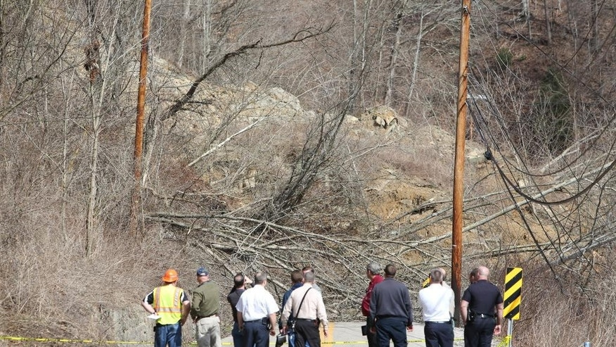 First responders assess a landslide on Keystone Drive, Thursday, March 12, 2015, in Charleston, W.Va.   A landslide broke loose, taking out power lines, trees, an unoccupied home, as well as a church. It also caused a nearby creek to rise. No injuries were reported and no flights at the airport were affected.  (AP Photo/The Daily Mail, Marcus Constantino)
