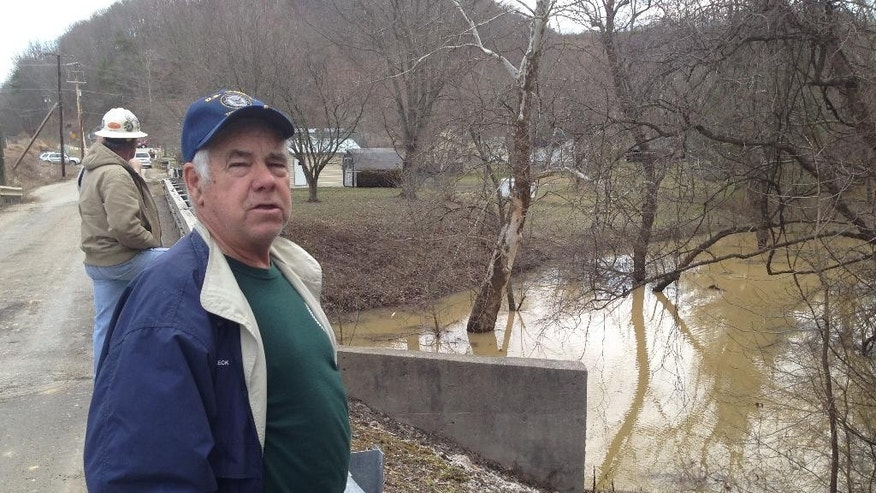 Clarence Fleck discusses concerns about a creek near his home in Charleston, W.Va., on Friday, March 13, 2014. A landslide near the end of a hilltop runway at Yeager Airport above his home broke loose Thursday, taking out power lines, trees, an unoccupied home, and a church. It also caused the nearby creek to rise and forced Fleck and others from their homes as a precaution. (AP Photo/John Raby)