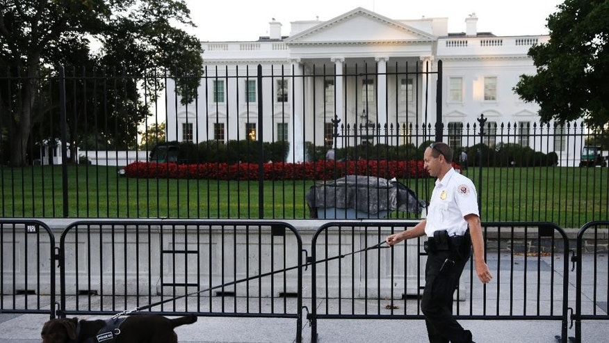 FILE - In this Sept. 22, 2014, file photo, a member of the Secret Service Uniformed Division with a K-9 walks along the perimeter fence along Pennsylvania Avenue outside the White House in Washington. Omar Gonzalez, 43, a knife-carrying Army veteran who scaled a White House fence and dashed into the executive mansion before being caught took a plea deal Friday, March 13, 2015. Gonzalez pleaded guilty to two federal charges. The Sept. 19 incident in which Gonzalez made it into the mansion's East Room preceded the disclosure of other serious Secret Service breaches in security for President Barack Obama and ultimately led to Julia Pierson's resignation as director of the agency. (AP Photo/Carolyn Kaster, File)
