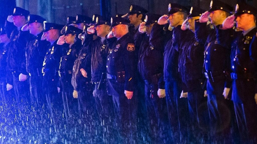 Law enforcement officers salute the arrival of the remains of Philadelphia Police Officer Robert Wilson III before a funeral procession on Saturday, March 14, 2015, in Philadelphia. City officials said on March 5, 2015 Wilson was shot and killed after he and his partner exchanged gunfire with two suspects trying to rob a video game store.  (AP Photo/Matt Rourke)