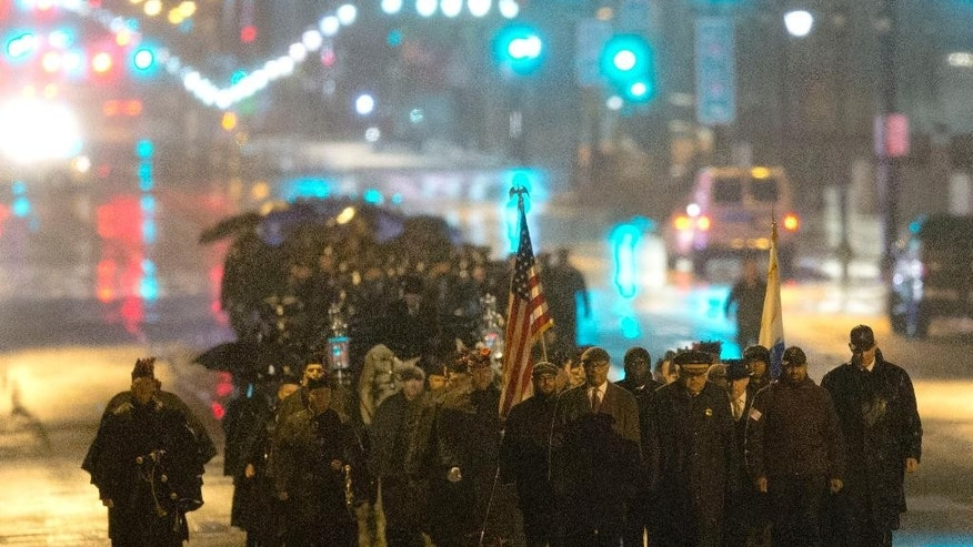 Philadelphia Police Officer Robert Wilson III funeral procession marches along Market Street during a winter rainstorm on Saturday, March 14, 2015, in Philadelphia. City officials said on March 5, 2015 Wilson was shot and killed after he and his partner exchanged gunfire with two suspects trying to rob a video game store.  (AP Photo/Matt Rourke)