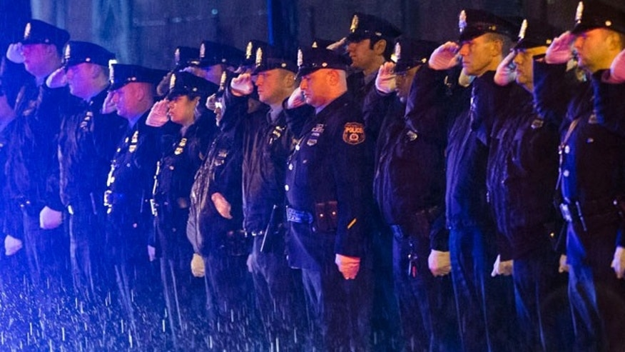 Mar. 5, 2015: Law enforcement officers salute the arrival of the remains of Philadelphia Police Officer Robert Wilson III before a funeral procession in Philadelphia. (AP)