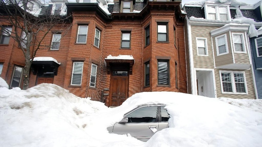 File-In this Feb. 23, 2015 file photo, a car remains buried in snow along a residential street in South Boston. Boston's miserable winter is now also its snowiest season going back to 1872. The official measurement of 108.6 inches at Logan International Airport Sunday night topped a season record of 107.9 inches set in 1995-96. The final 2.9 inches came in a snowstorm that was relatively tame after a record-setting monthly snowfall of 64.9 inches in February. (AP Photo/Elise Amendola, File)