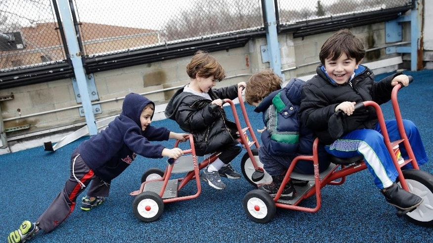 "Joey Arking, 5, left, Moshe Lib, 4, second from left,  Michael Skaba, 4, second from right and Leo Jajati, 4, play on the rooftop playground at the Al & Sonny Gindi Barkai Yeshivah in Brooklyn, New York, Wednesday, March 11, 2015. Starting next September, New York City pre-K classes will be permitted to break in the middle of the day for ""non-program"" activities such as prayer. Civil liberties groups say the prayer break in a publicly funded classroom may violate the constitutional separation of church and state.  (AP Photo/Seth Wenig)"