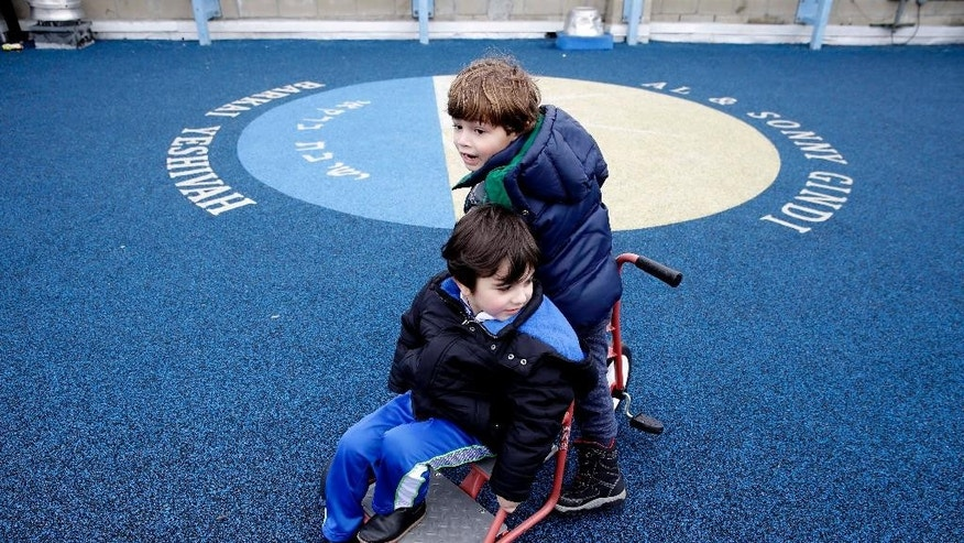 "Leo Jajati, 4, right, and Michael Skaba, 4, play on the rooftop playground at the Al & Sonny Gindi Barkai Yeshivah in Brooklyn, New York, Wednesday, March 11, 2015. Starting next September, New York City pre-K classes will be permitted to break in the middle of the day for ""non-program"" activities such as prayer. Civil liberties groups say the prayer break in a publicly funded classroom may violate the constitutional separation of church and state.  (AP Photo/Seth Wenig)"