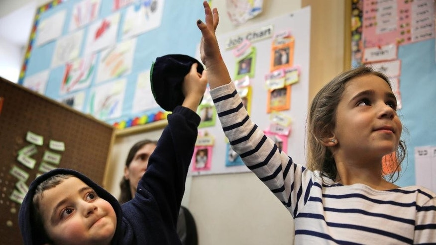 "Elyse Dweck, 4, right, and Joey Arking, 5, raise their hands in their pre-kindergarten class at the Al & Sonny Gindi Barkai Yeshivah in Brooklyn, New York, Wednesday, March 11, 2015. Starting next September, New York City pre-K classes will be permitted to break in the middle of the day for ""non-program"" activities such as prayer. Civil liberties groups say the prayer break in a publicly funded classroom may violate the constitutional separation of church and state.  (AP Photo/Seth Wenig)"