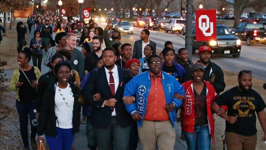 March 10, 2015: University of Oklahoma students march to the now closed University of Oklahoma's Sigma Alpha Epsilon fraternity house  during a rally in reaction to an incident in which members of a fraternity were caught on video chanting a racial slur, in Norman, Okla. (AP)