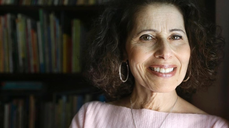 "In this Wednesday, March 11, 2015 photo, author Leslea Newman, of Holyoke, Mass., stands for a portrait at her home in Holyoke. Newman wrote the book ""Heather Has Two Mommies,"" 25 years ago about a little girl named Heather and her two happy mommies that became a cultural and legal flashpoint. Newman has updated the book with fresh illustrations from a new artist. (AP Photo/Steven Senne)"
