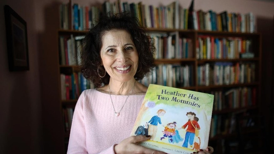 "In this Wednesday, March 11, 2015 photo, author Leslea Newman, of Holyoke, Mass., displays a copy of her book ""Heather Has Two Mommies,"" in Holyoke. Newman, who wrote the original version of ""Heather Has Two Mommies,"" 25 years ago, about a little girl named Heather and her two happy mommies, has updated the book with fresh illustrations from a new artist. (AP Photo/Steven Senne)"