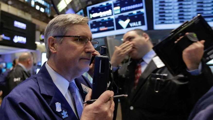 Trader Christopher Fuchs, left, works on the floor of the New York Stock Exchange, Monday, March 16, 2015. U.S. stocks opened higher, led by health care and utilities companies, rebounding after three weeks of losses. (AP Photo/Richard Drew)