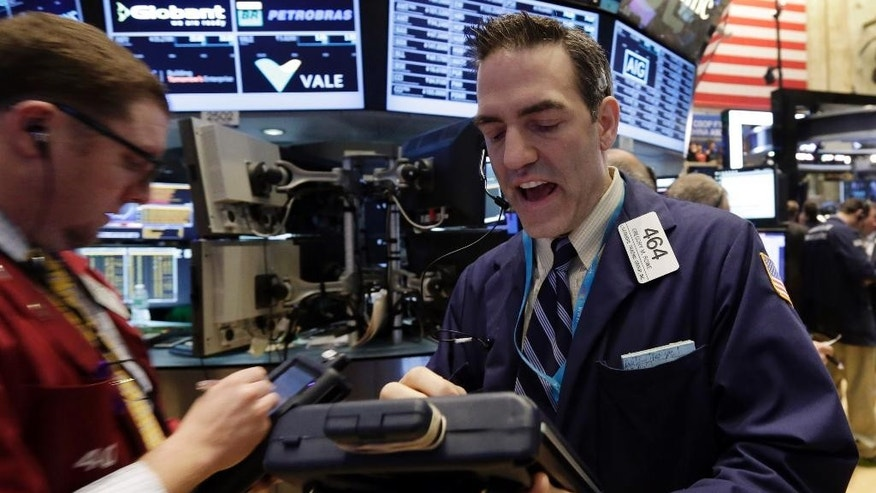 Trader Gregory Rowe, right, works on the floor of the New York Stock Exchange, Monday, March 16, 2015. U.S. stocks opened higher, led by health care and utilities companies, rebounding after three weeks of losses. (AP Photo/Richard Drew)