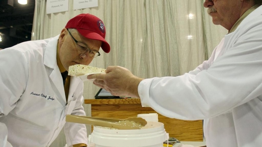 Judge Stan Dietsche, right, lets another judge, Tim Czmowski, smell a flavored feta cheese during the 2015 United States Championship Cheese Contest, Tuesday, March 17, 2015, in Milwaukee. The contest is the biggest ever, with a record 1,885 entries from 28 states. (AP Photo/Carrie Antlfinger)