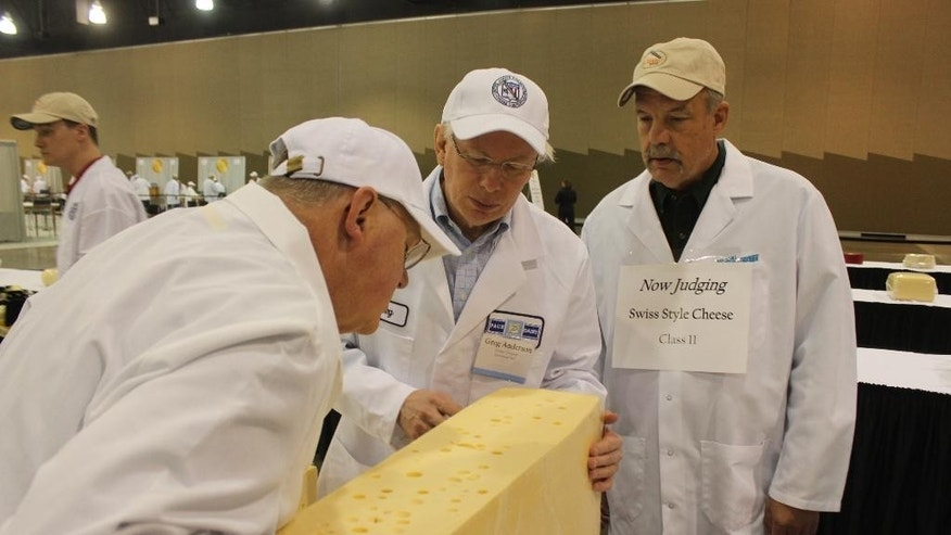 From left,  judges Doug Anker and Greg Anderson, and volunteer Steve Stettler inspect a swiss cheese during the 2015 United States Championship Cheese Contest on Tuesday, March 17, 2015 in Milwaukee. The contest is the biggest ever, with a record 1,885 entries from 28 states. (AP Photo/Carrie Antlfinger)