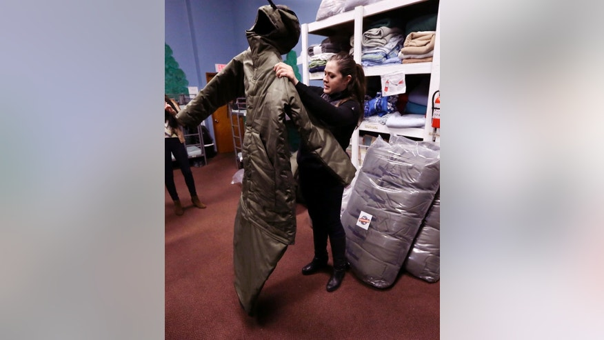 In a Tuesday, March 3, 2015 photo, Veronika Scott of The Empowerment Plan Detroit, demonstrates her sleeping bag coat to people at a homeless shelter in Pontiac, Mich. Scott, a former design student, is trying to help the homeless population in two distinct ways by employing and training homeless women to manufacture a garment that serves as both a coat and a sleeping bag. The coats then are distributed back to homeless people at no cost to them. (AP Photo/Carlos Osorio)