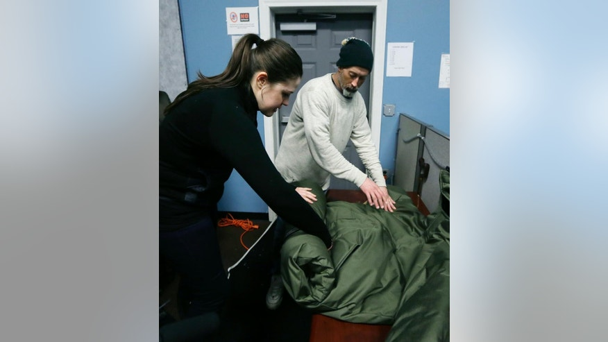 In a Tuesday, March 3, 2015 photo, Veronika Scott of The Empowerment Plan Detroit, demonstrates how to roll up her sleeping bag coat to people at a homeless shelter in Pontiac, Mich. Scott, a former design student is trying to help the homeless population in two distinct ways by employing and training homeless women to manufacture a garment that serves as both a coat and a sleeping bag. The coats then are distributed back to homeless people at no cost to them. (AP Photo/Carlos Osorio)