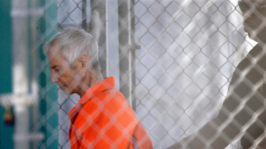 Robert Durst is escorted into Orleans Parish Prison after his arraignment in Orleans Parish Criminal District Court in New Orleans, Tuesday, March 17, 2015.  Durst was rebooked on charges of being a convicted felon in possession of a firearm, and possession of a weapon with a controlled dangerous substance, a small amount of marijuana.  (AP Photo/Gerald Herbert)