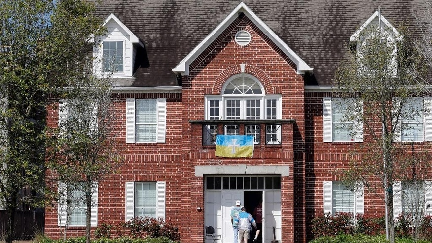 Men walk into the Sigma Chi fraternity house after the University of Houston suspended the fraternity Wednesday, March 18, 2015, in Houston, Texas. The University of Houston president  announced Tuesday that the Sigma Chi chapter and five of its student members have been suspended and that an investigation into pledge activity is ongoing. (AP Photo/David J. Phillip)