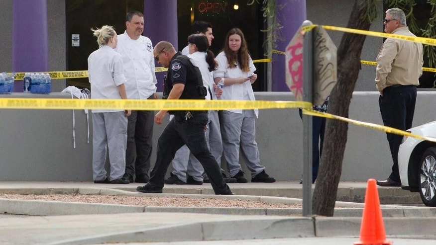 Mesa police talk to eyewitnesses at the scene of a shooting, Wednesday, March 18, 2015, in Mesa, Ariz. A gunman wounded at least four people across multiple locations in the Phoenix suburb and police warned residents to stay indoors as they hunt for the suspect. (AP Photo/The Arizona Republic, Nick Oza)