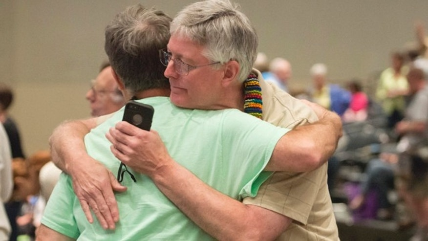 FILE - In this June 19, 2014, file photo, Gary Lyon, left, of Leechburg, Pa., and Bill Samford, of Hawley, Pa., celebrate after a vote allowing Presbyterian pastors discretion in marrying same-sex couples at the 221st General Assembly of the Presbyterian Church at Cobo Hall, in Detroit. (AP Photo/Detroit News, David Guralnick, File)