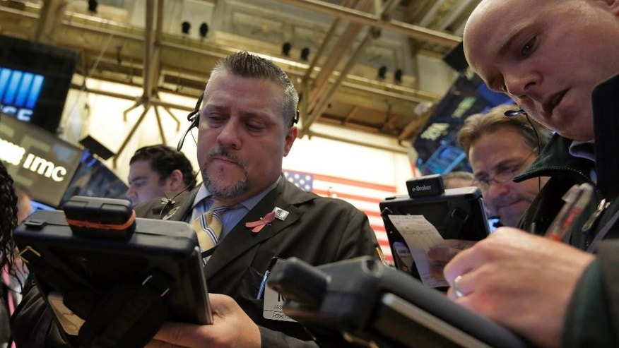 Jason Harper, left, works with fellow traders on the floor of the New York Stock Exchange, Wednesday, March 18, 2015. Stocks are falling for the second day in a row as traders try to guess when U.S. interest rates will rise. (AP Photo/Richard Drew)