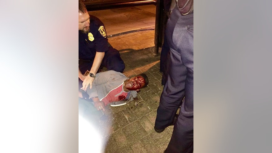 In this photo provided by Bryan Beaubrun, Martese Johnson is held down by an officer Wednesday, March 18, 2015, in Charlottesville, Va. Court records show that Johnson was charged with obstruction of justice without force and public swearing or intoxication. The Virginia Gov. Terry McAuliffe is calling for an investigation into the arrest of the student. (AP Photo/Bryan Beaubrun)